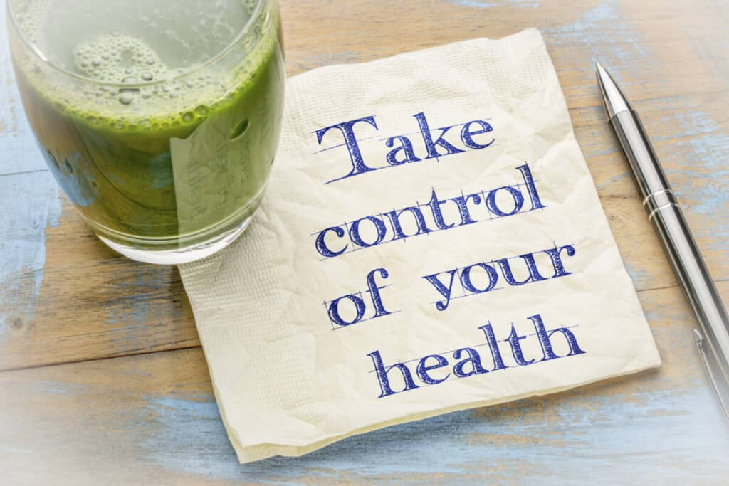 Take control of your health advice - handwriting on a napkin with a glass of whey isolate shake