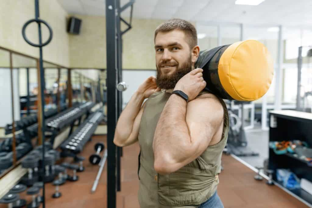 Portrait muscular bearded adult man in gym, dressed in a plate carrier with weight vest plates
