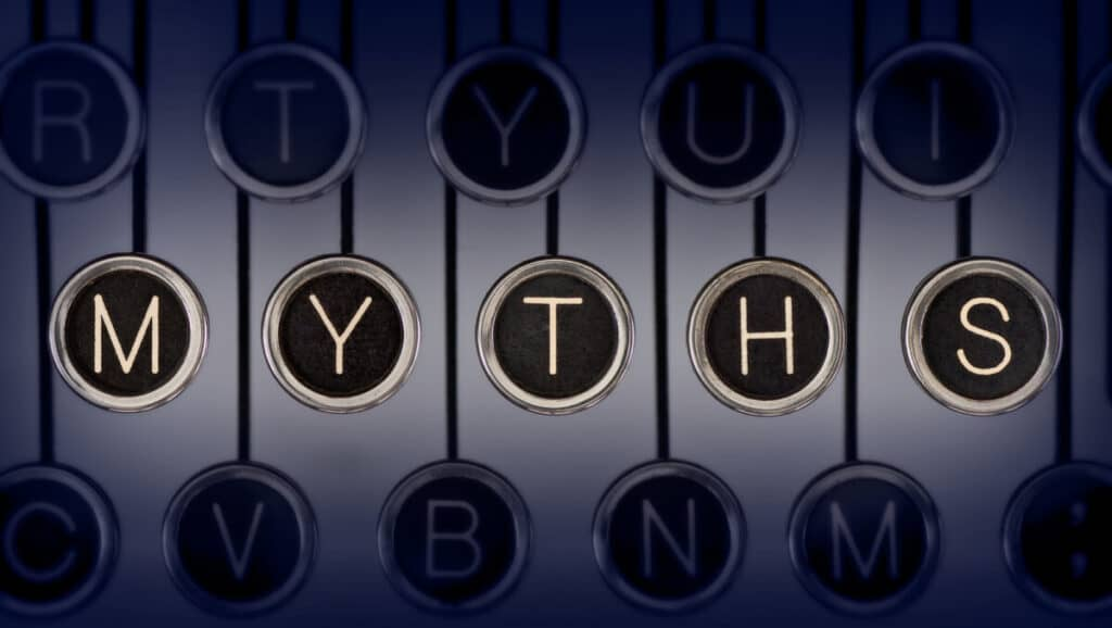 "Close up of old manual typewriter keyboard with scratched chrome keys that spell out ""MYTHS"".  Lighting and focus are centered on ""MYTHS""."