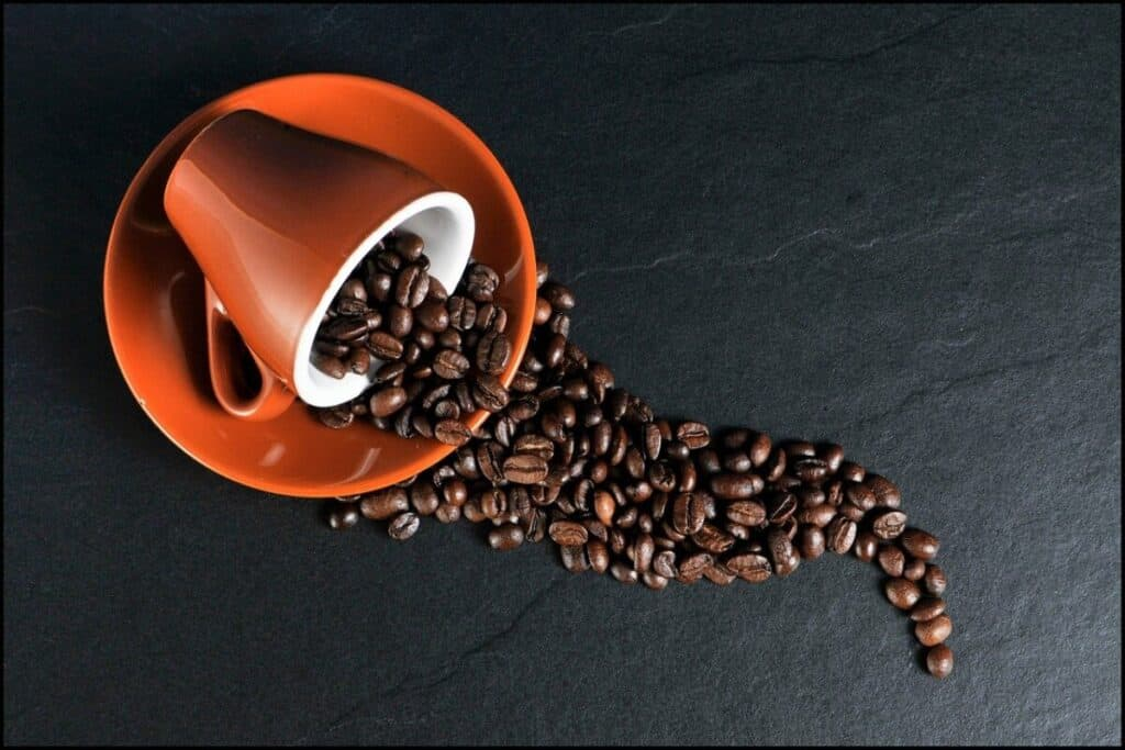 A coffee cup on a saucer tipped over spilling coffee beans out which is an ingredient in fat burners.