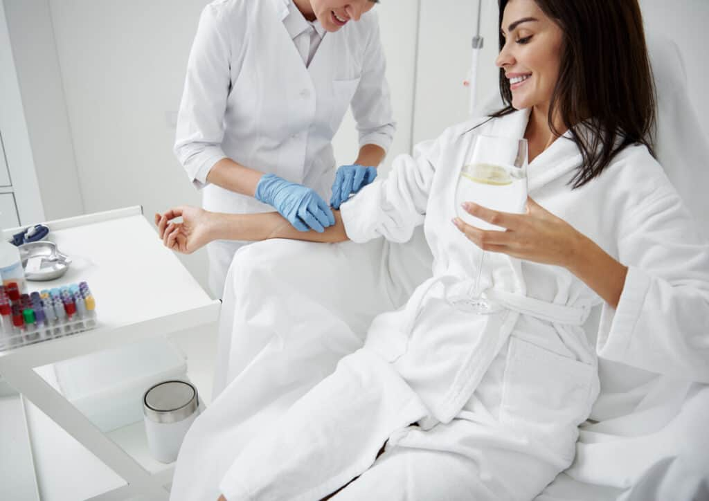Cropped portrait of beautiful woman in white bathrobe sitting in armchair and receiving IV infusion of vitamin C She is holding glass of beverage with lemon and smiling