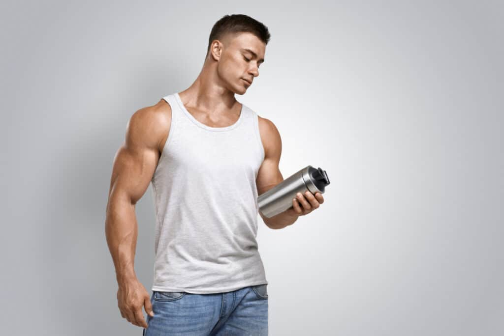 Muscular fitness male bodybuilder holding protein shake bottle comparing whey concentrate vs isolate ready for drinking. Studio shot on white background
