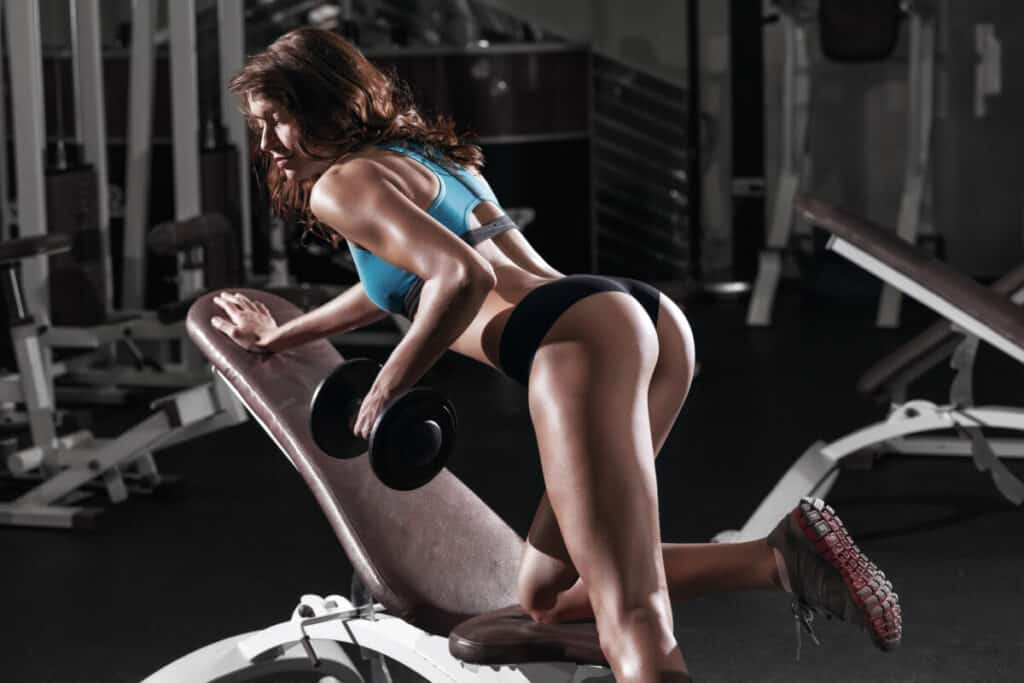 brunette kneeling on a weight bench  doing dumbbell rows