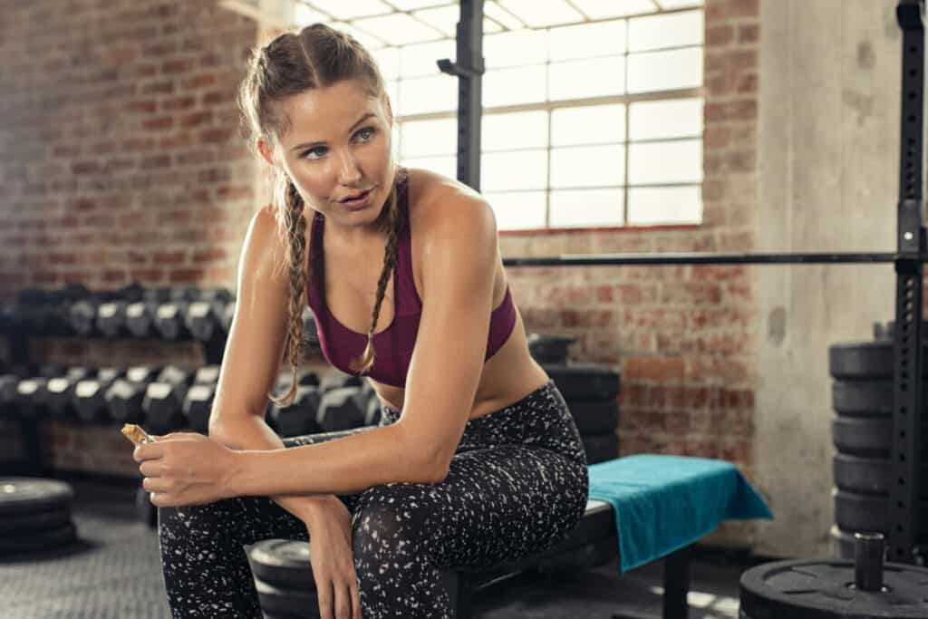 A fit young woman eating a proteiar post workout to give herself more energy