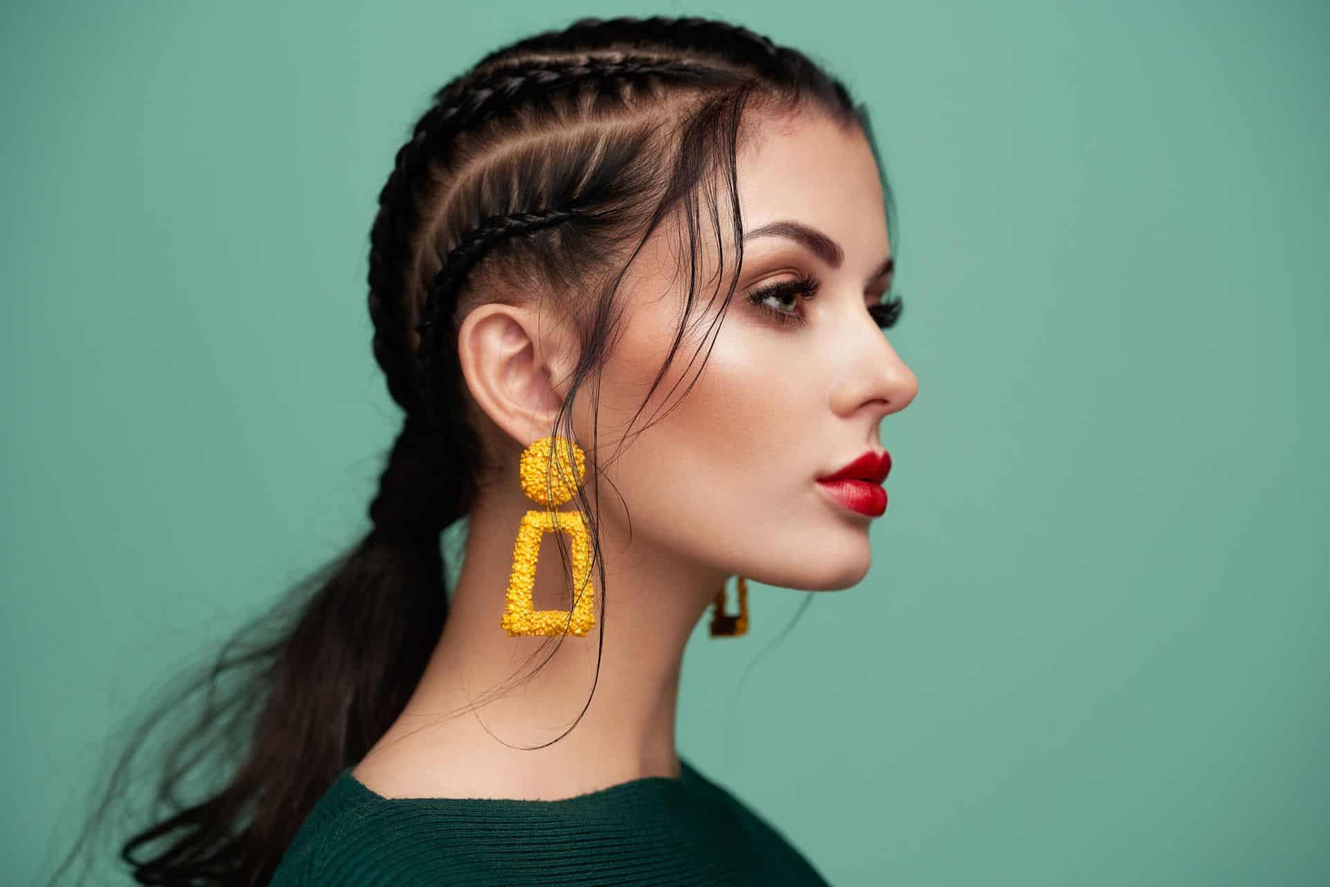 Des boucles d'oreilles élégantes et colorées pour une coiffure avec des tresses.