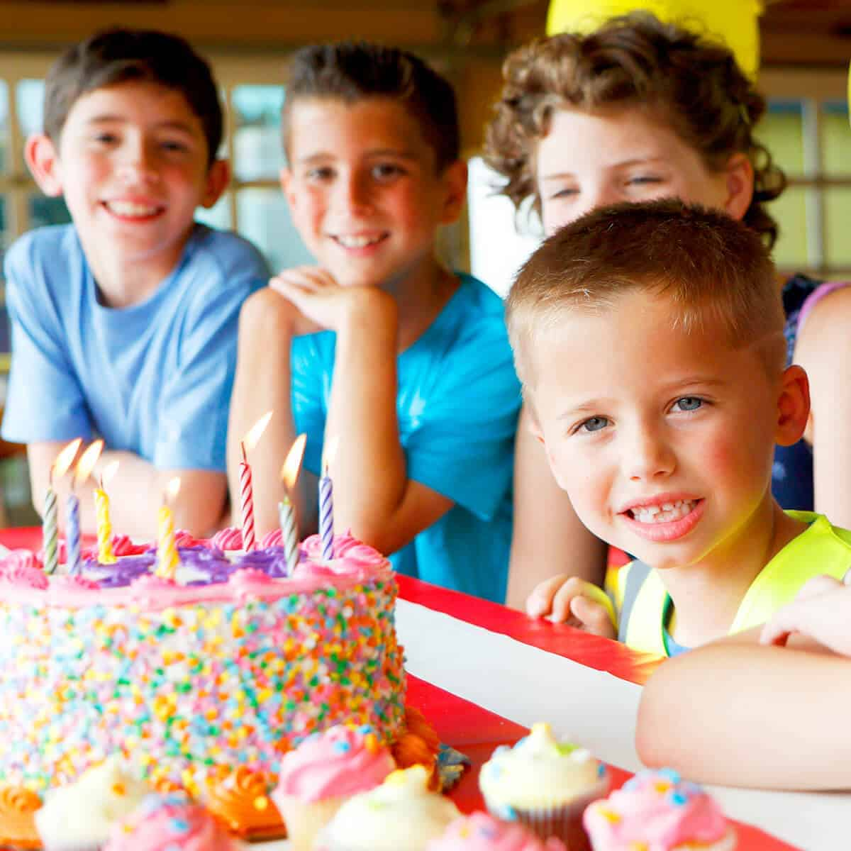 Birthday boy ready to blow out candles on colorful cake