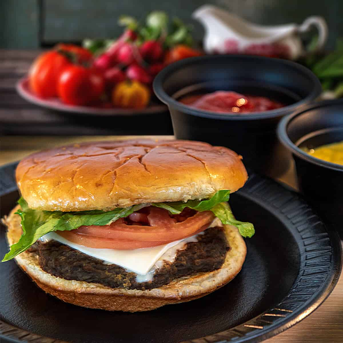 Cheeseburger on bun with tomatoes and lettuce and chips
