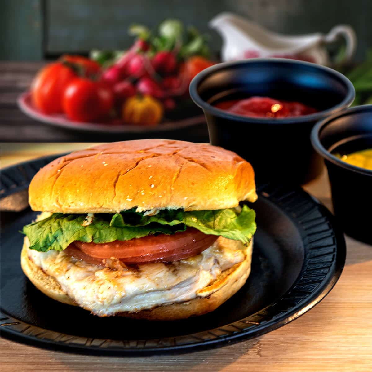 Chicken breast on a bun with tomatoes ad lettuce