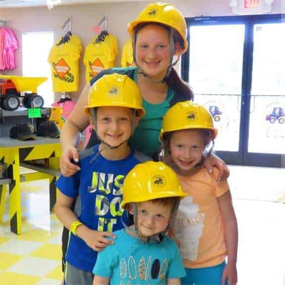 Girls and boys wearing yellow hard hats with Diggerland logo