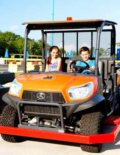 Rugged rider RTV being driven by a boy and girl on a sunny day