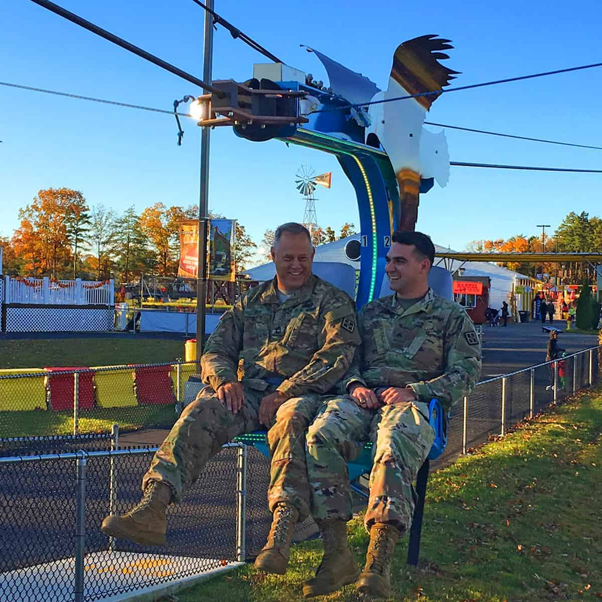 Two military personnel riding the Soaring Eagle zip line