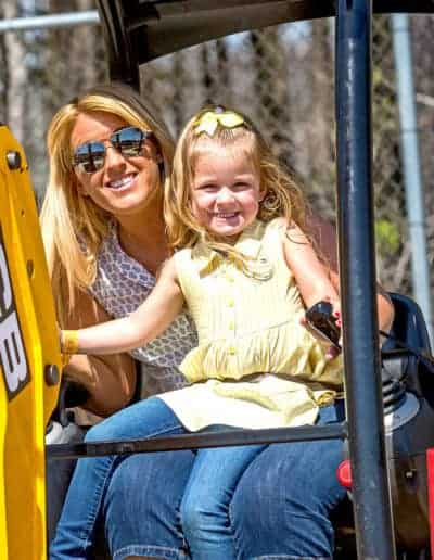 Happy mother and daughter lap riding the Mini Digger