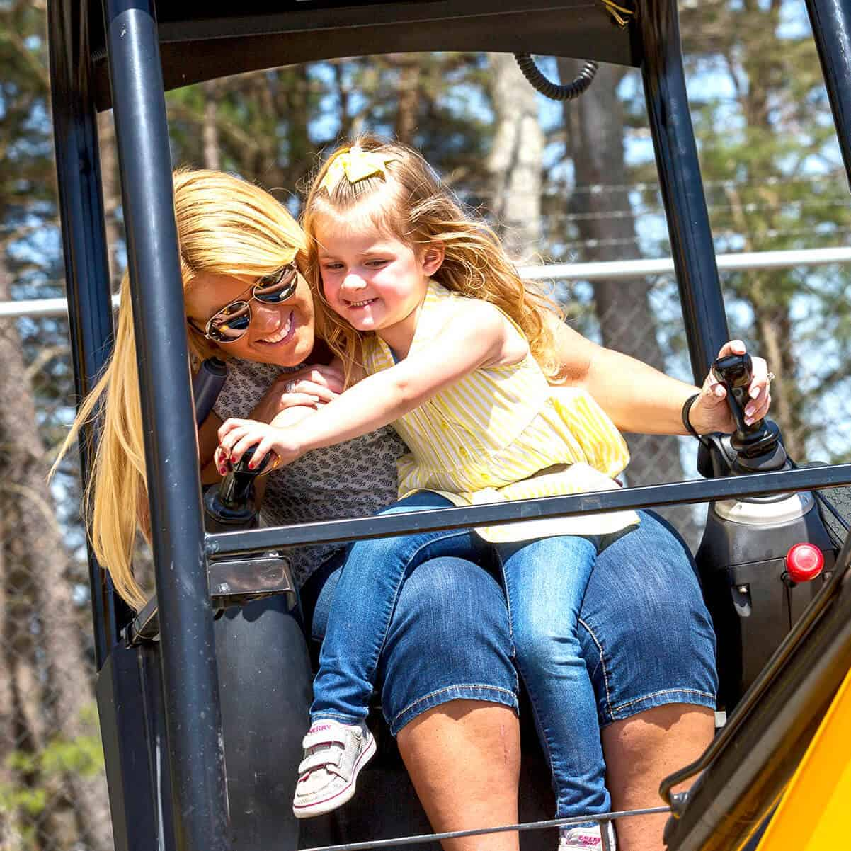 Mom and daughter smiling and playing on mini digger games