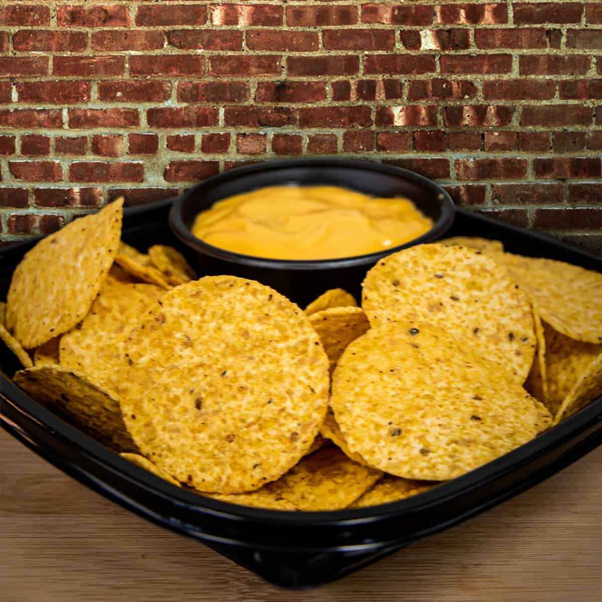 Basket of nachos with serving of cheese