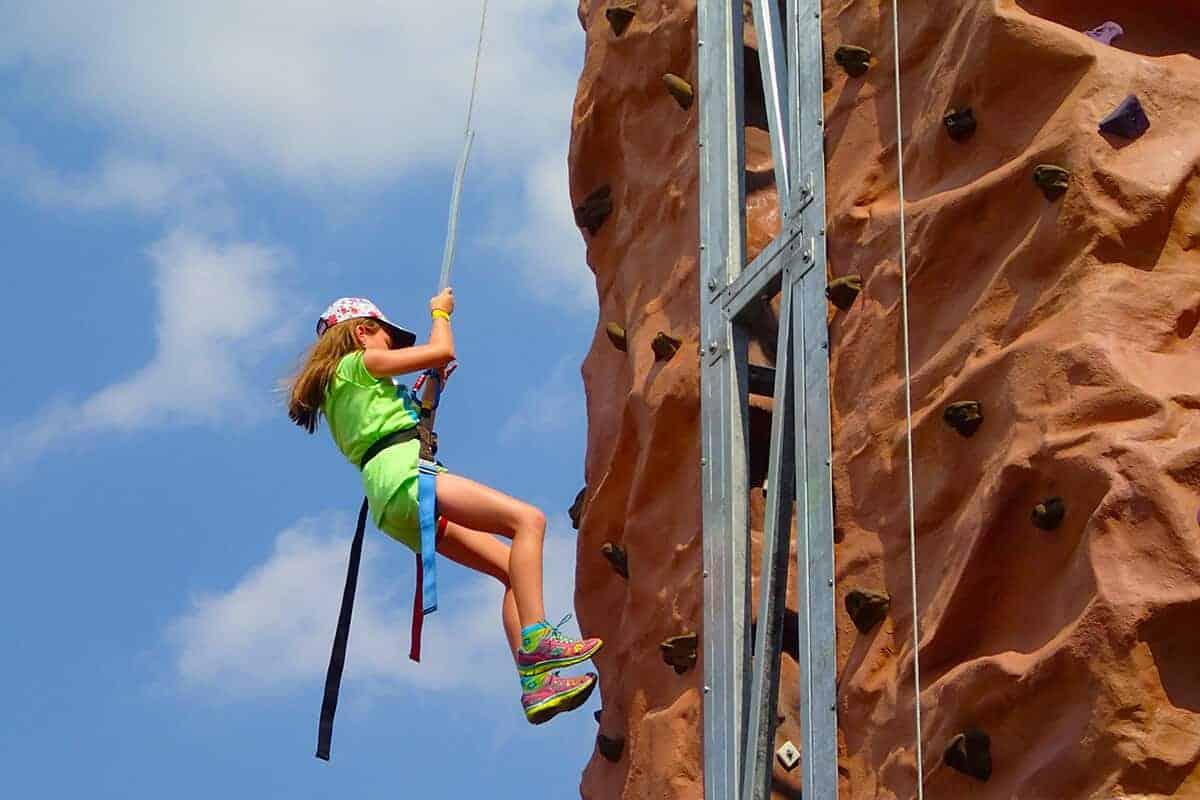 Girl climbs side of rock wall at Diggerland USA