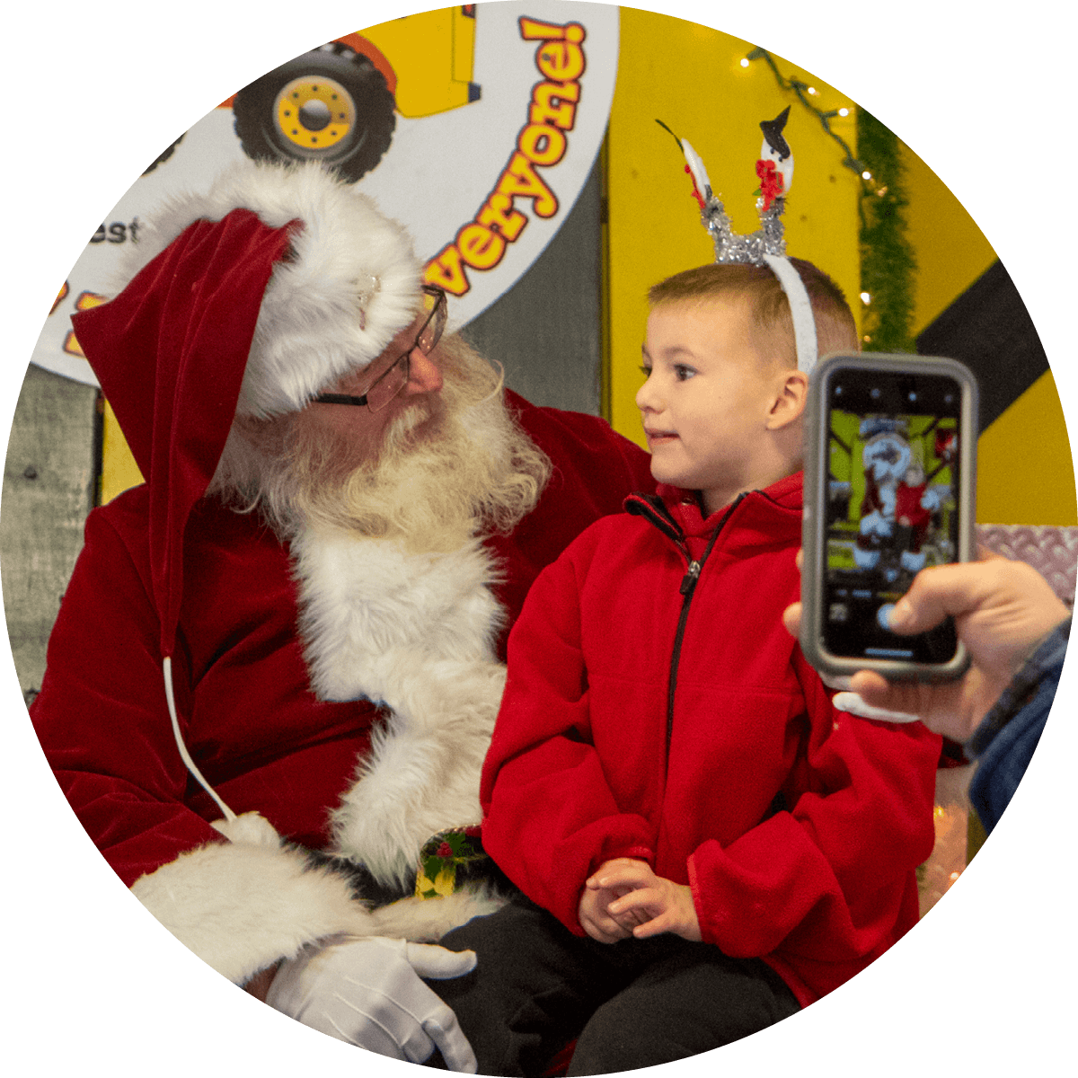 Child on Santa's lap telling him what he wants for Christmas while Dad takes photo.