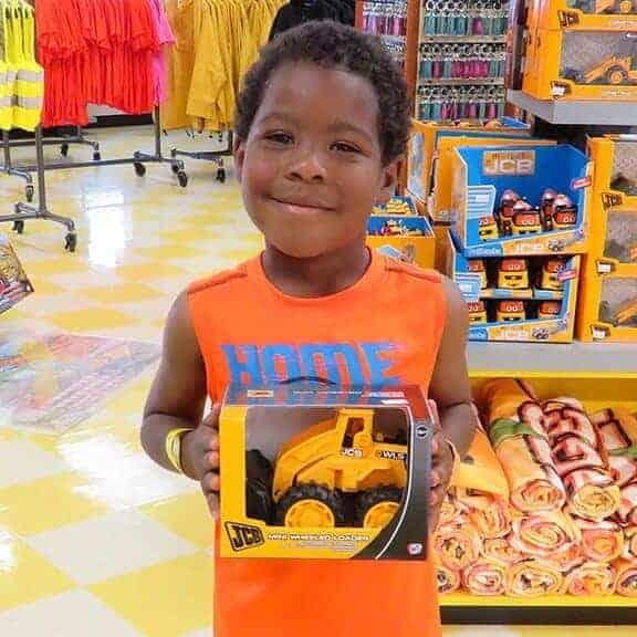 Boy holding JCB mini wheel loader in packaging