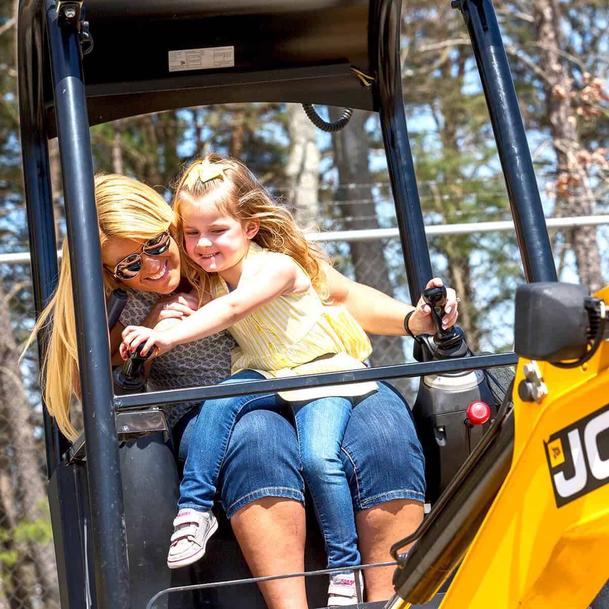 Mini digger with woman and child operating