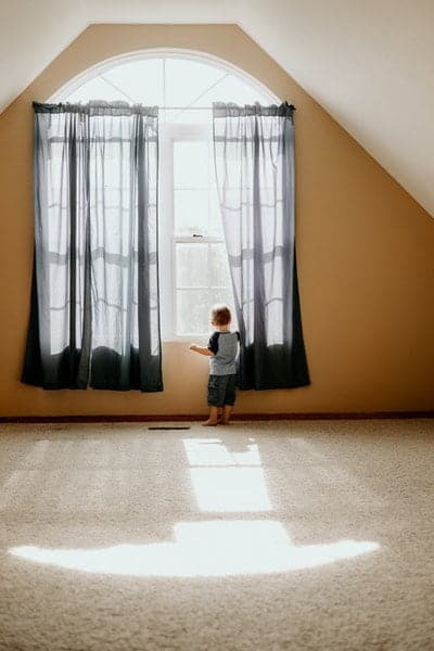 A baby standing next to a window