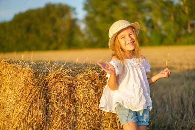 country girl standing next to hay roll