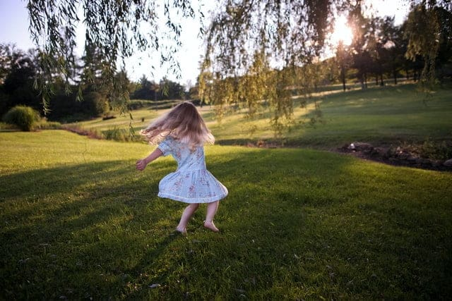 A toddler dancing out in the fields alone