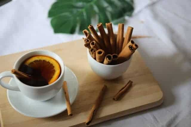 A cup of cinnamon tea and cinnamon sticks. does cinnamon cause miscarriages