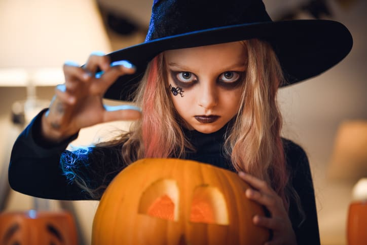 young girl wearing a witch costume