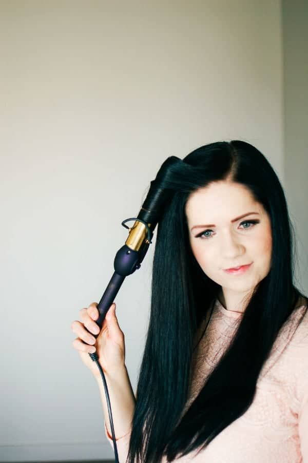 A woman shows her hair curling tutorial for long hair.