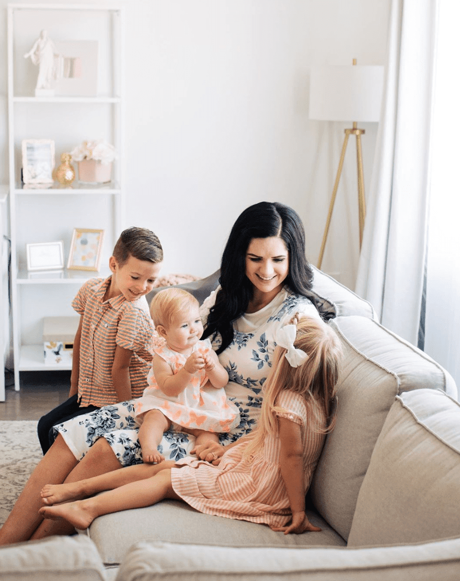 Mom with kids on living room couch.