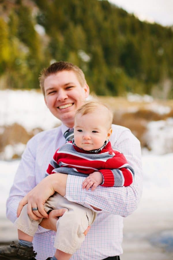 Dad holds baby boy during photo shoot in the mountains.
