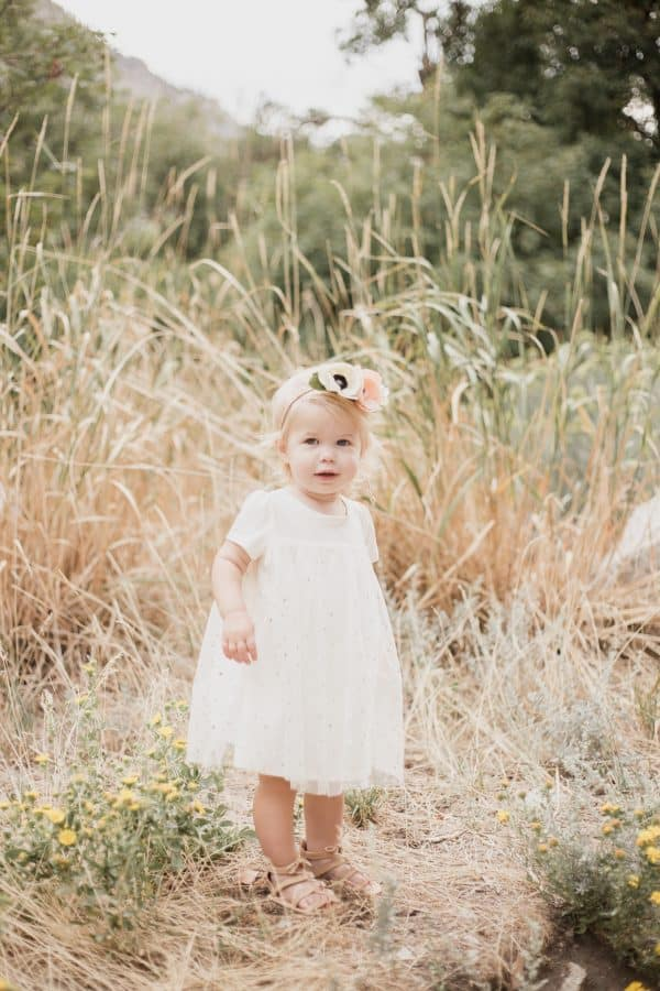 Baby girl poses during family pictures.