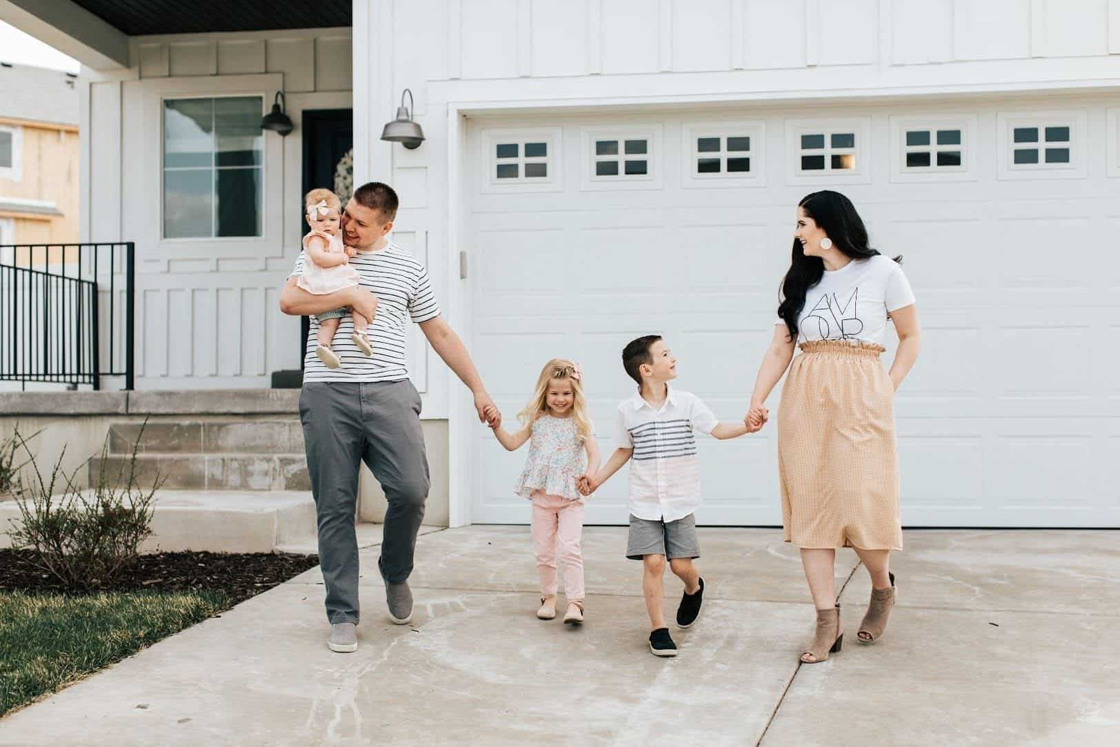 Family walks down driveway during summer family photos.