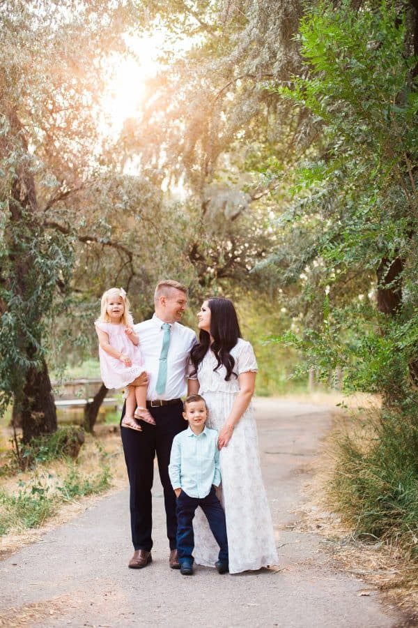 Family wears turqouise, pink, and white during family photos.