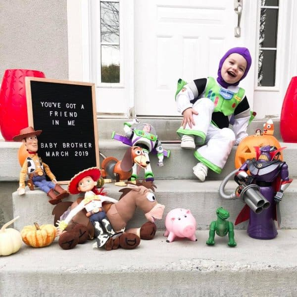 Boy dressed as Buzz Lightyear sits by Toy story characters for a gender reveal