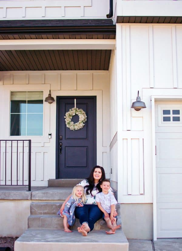 A young homeowner sits with her two kids in front of their new house.