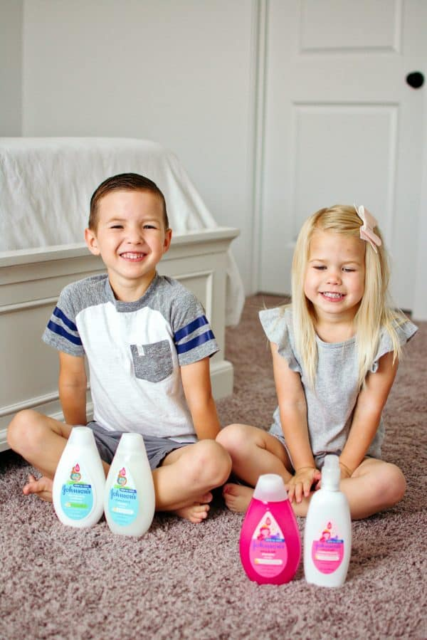 Two children sit with their kids hair products.