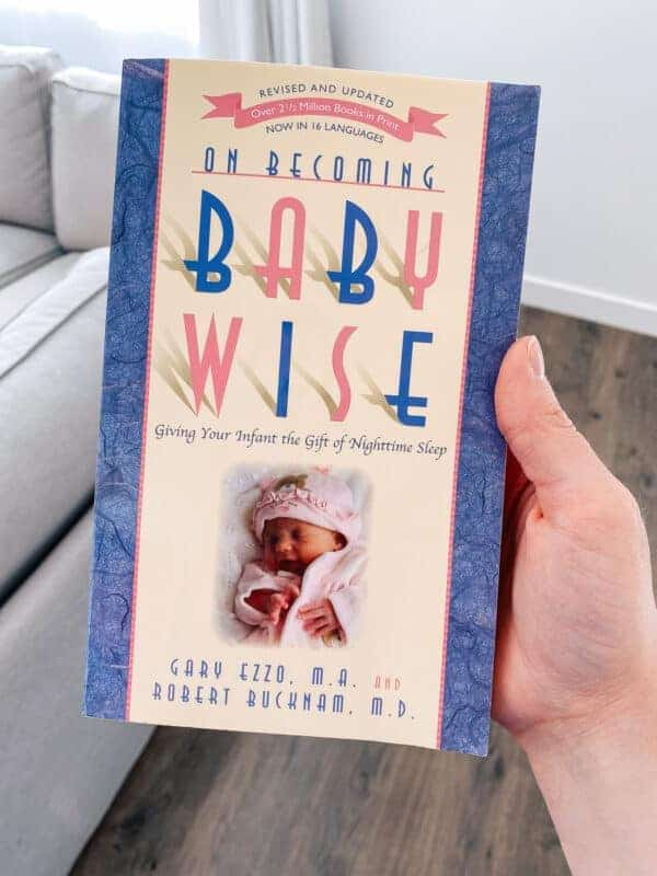 Mom holds Babywise book that she uses to sleep train her newborn.