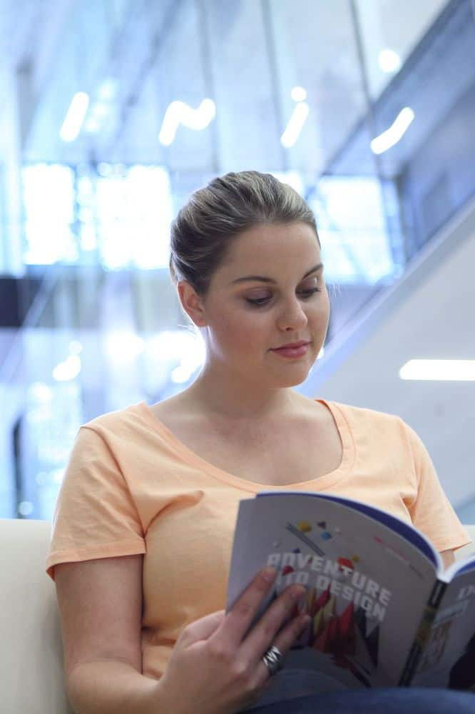 A woman reads a magazine in the Lifehouse lobby