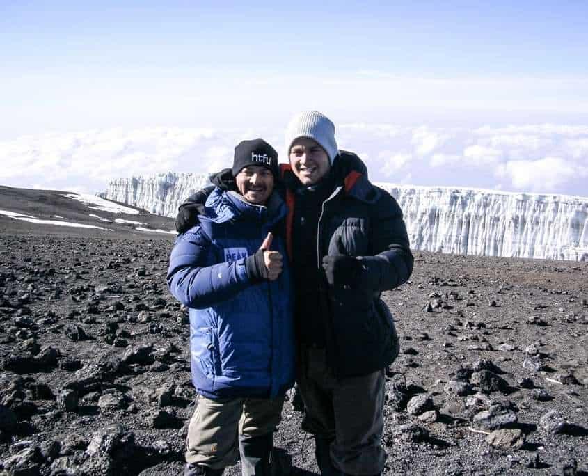 Luke standing on the summit after climbing Mount Kilimanjaro with Shane Pophfer