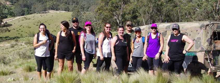 The Peak Potential Adventures group photo with Megalong Valley and the Blue Mountains in the distance as they trek along the Six Foot Track