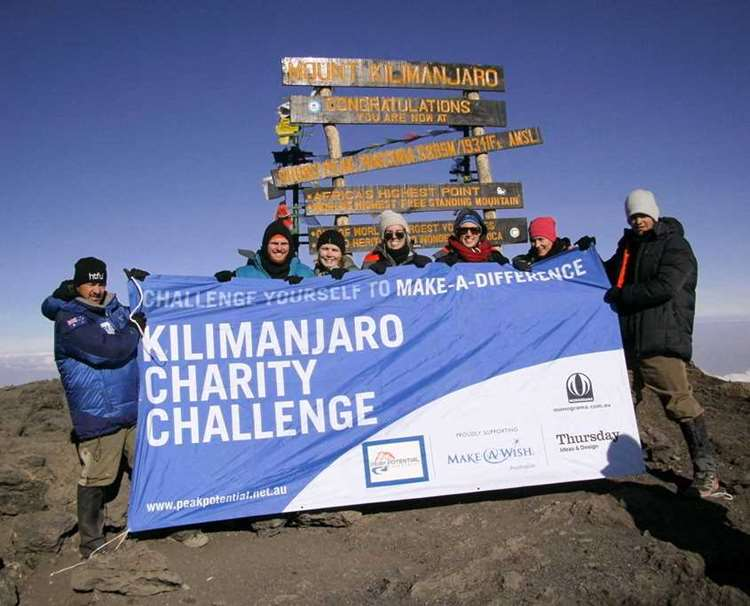 The team getting a summit photo on Mt Kilimanjaro in Africa