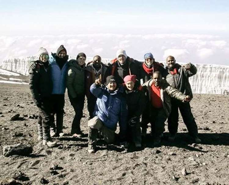A photo of our team celebrating their summit success of Mt Kilimanajro in Africa