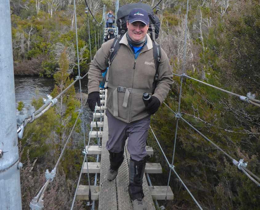 Michael Donovan walking across a suspension bridge on the Overland Track