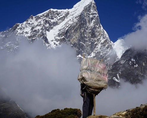 A photo of a porter with Ama Dablam in the background in the Himalayas
