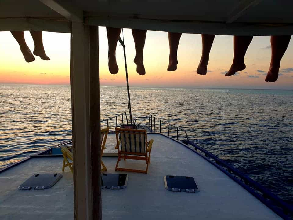 maldives sunset - 4 sets of feet dangling over boat