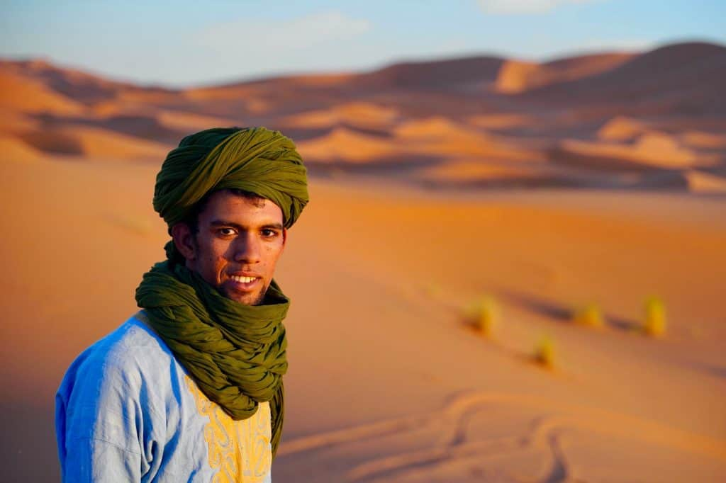 camel guide in the sunset on sand dunes in morocco