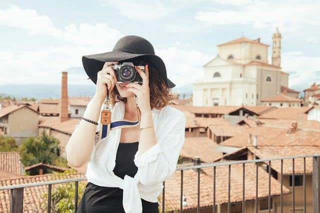 best cameras for backpacking - lady is pointing camera forwards with a mediterranean town in the background