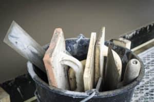 välvårdade murarverktyg i hink