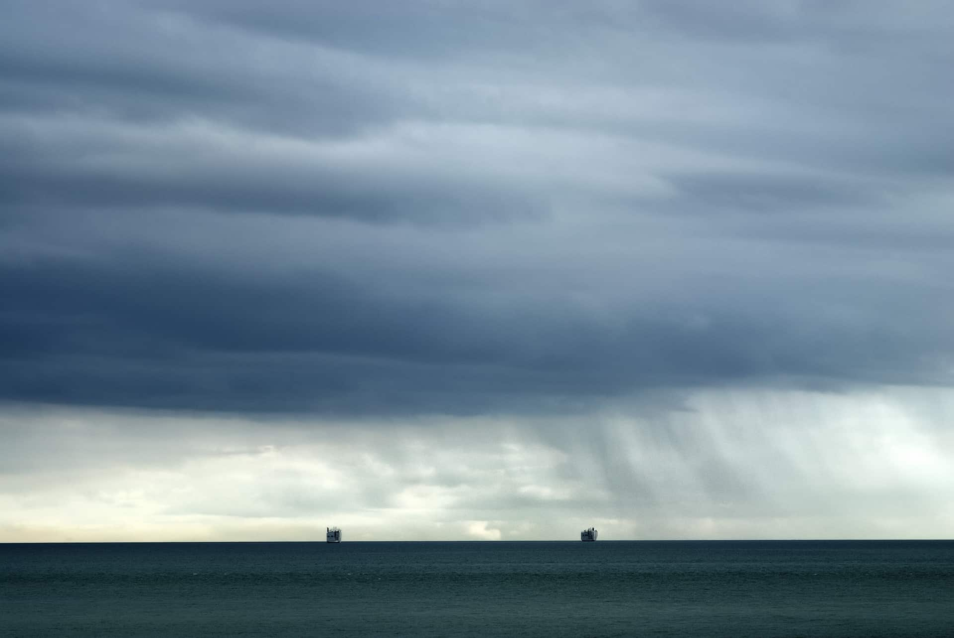 Rainclouds and two tankers at sea off the coast of Bembridge, Isle of Wight , england, UK