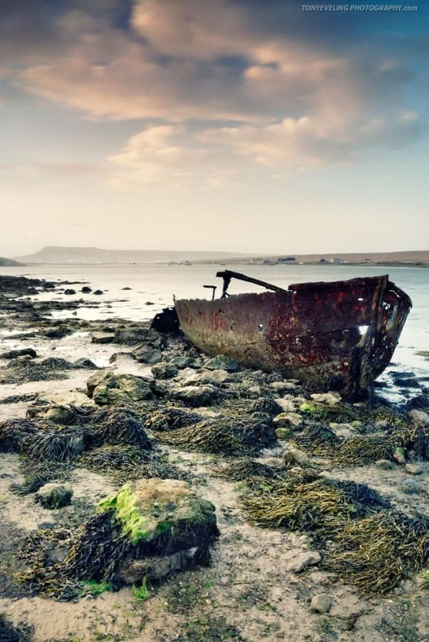 Abandoned and rusty boat in the Fleet lagoon, Chesil beach, Dorset, England, UK